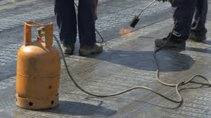 two construction workers using gas torch and welding bitumen for