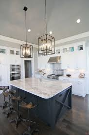 325 best white kitchen cabinets inspiration images on pinterest white and navy kitchen features iron and glass cage lanterns over navy center island accented with x trim moldings topped with white and gray stone