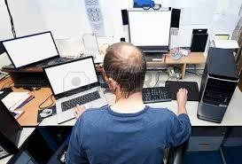 Computer Technician Desk Portrait Of A Stern Looking Computer Technician In An Untidy