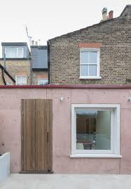 pink concrete extension adds warmth and texture to brick house in