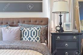 cozy bedroom interior with pillows and reading lamp on bedside