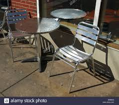 Outdoor Metal Tables And Chairs Outdoor Metal Table Chairs On Cement Walk Near Brick Wall Modern