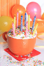 happy birthday cup cake with lit candles and balloons stock photo