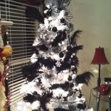 a black tree covered with silver ornaments all for a bold