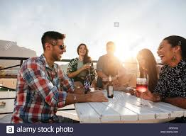 multiracial group of friends having cocktail party on the rooftop