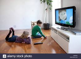 sister and brother watching tv at home stock photo royalty free