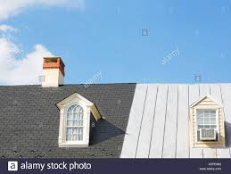 two windows and a chimney on two continuous house roofs stock