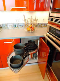 unique kitchen cabinet with glossy orange cabinets black pan in it