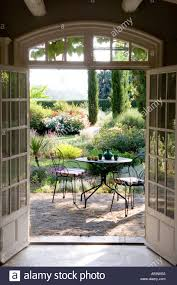 sunlit cafe style table and chairs set on garden terrace in