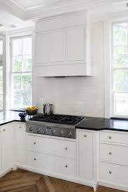 Kitchens With White Cabinets And Black Countertops by White Kitchen Cabinets With Brass Hardware And Black Countertops