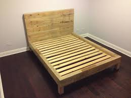 brown wooden reclaimed wood bed frame in a small bedroom of