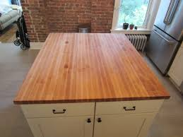 brown butcher block on white wooden island with doors and drawers