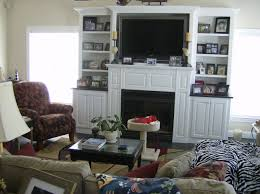 black fireplace in the middle of white wooden shelves combined