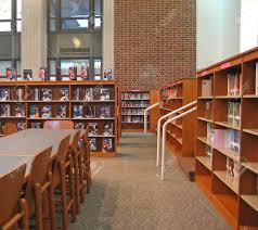 library with bookshelves tables chairs and high ceiling