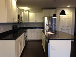 kitchen with white shaker cabinets black quartz countertops