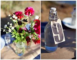 wedding flowers jam jars keeping the table details simple with luggage tags and flowers in