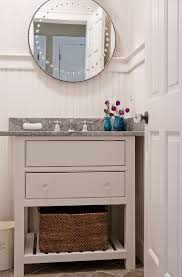 bathroom painted wood wall with round wall mirror and garnite