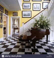 Checkerboard Vinyl Floor Tiles by Large Flower Arrangement On Grand Piano In Yellow Country Hall