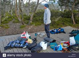 hiker and luggage on tent platform near lake windermere on