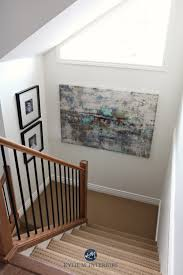 stairwell with beige carpet wood and metal railing and sherwin