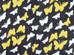 white and yellow butterfly pattern on black fabric background