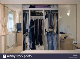shared built in bedroom wardrobe with mirror sliding doors open to shared built in bedroom wardrobe with mirror sliding doors open to show garments on hanging rail