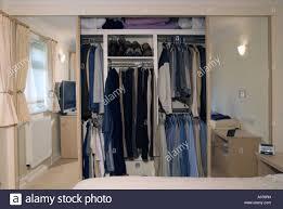 shared built in bedroom wardrobe with mirror sliding doors open to