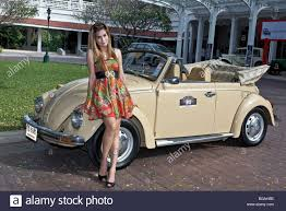 volkswagen car beetle old female model posing with a classic cream coloured volkswagen