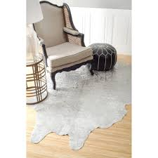 decorating exciting cow hide rug on kahrs flooring and mid beige wingback chair with dark wood frame and