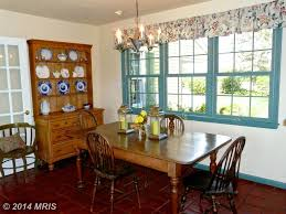 country dining room with chandelier u0026 terracotta tile floors in
