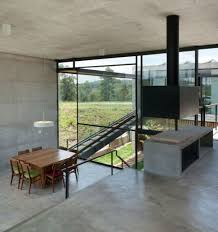 hillside house with 2 concrete volumes 2nd story entrance bridge