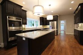 kitchen with wood floor dark cabinets light countertops and