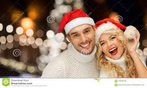 happy couple in santa hats over christmas lights stock image