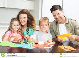 smiling family doing arts and crafts together at the table stock