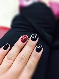 black gel with red glitter on ring finger on natural nails