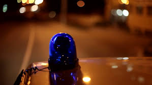 blue light on car blue emergency light on the roof of a police car riding down the
