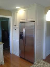 close up of stainless steel refrigerator and white painted pantry