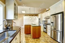 bright kitchen room with granite tops kitchen island and white