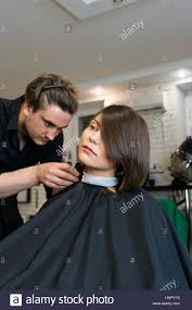 male hairdresser does a haircut to pretty woman in the beauty