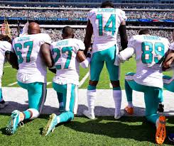 nfl players kneel raise fists lock arms during national anthem