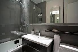 white corner bathtub and white ceramic water closet on black tiled