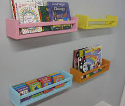 pink blue with yellow and orange wooden wall shelves with books