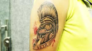 ancient greek warrior helmet tattoo inked by black poison