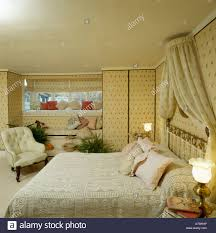 coronet drapes above bed with lace bedlinen in bedroom with