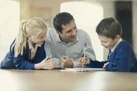 Father helping children with homework Verywell