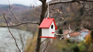 a miniature painted decorative bird house ornament hanging outside