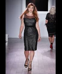 a plus size model walks the runway as she models clothing from the