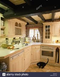corner of cream cottage kitchen with built in dishwasher and oven