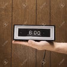 retro wood paneling caucasion male hand holding retro clock set for 6 00 against