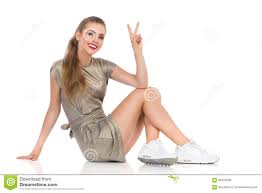 woman in gold mini dress showing peace sign stock photo image